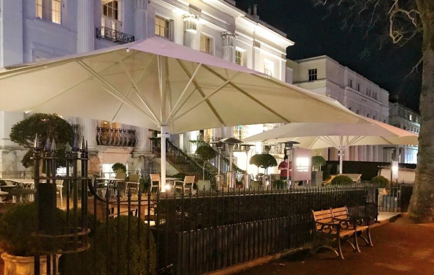 2 large white umbrellas outside bar