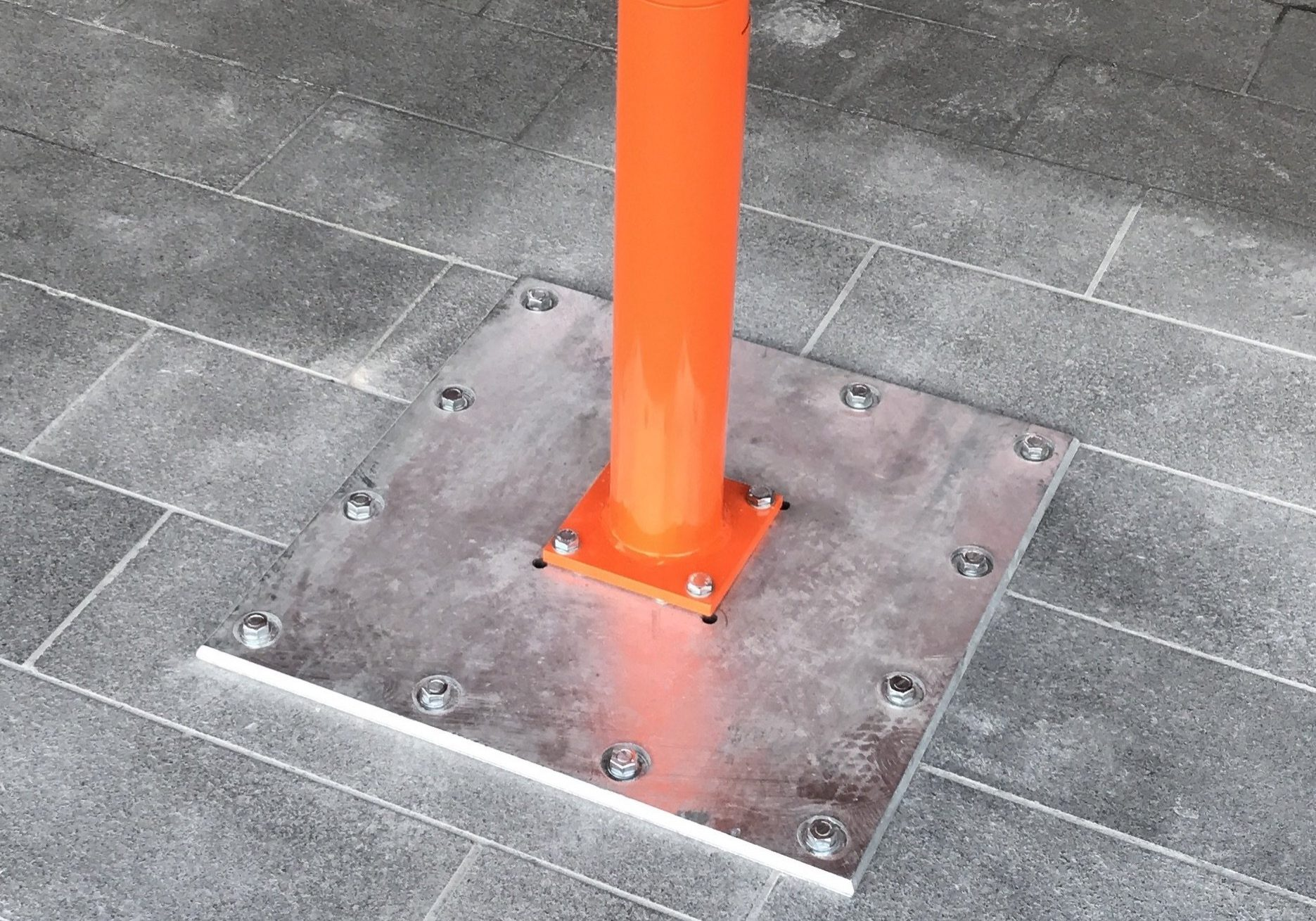 Orange Umbrella pole bolted to ground